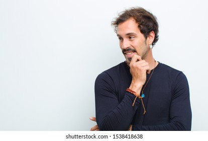 young handsome man smiling with a happy, confident expression with hand on chin, wondering and looking to the side against white wall