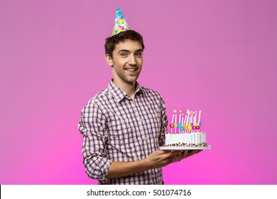 Young handsome man smiling, holding birthday cake over purple background.