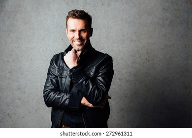 Young handsome man smiling  isolated against concrete wall