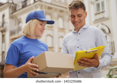 Young handsome man smiling joyflly, signing delivery papers ona  clipboard, receiving postal box from a female courier. Delivery woman working in the city