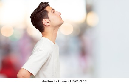 young handsome man smiling and looking upwards, towards the sky or to the spot where the publicist may place a concept or message. Lateral rear view.