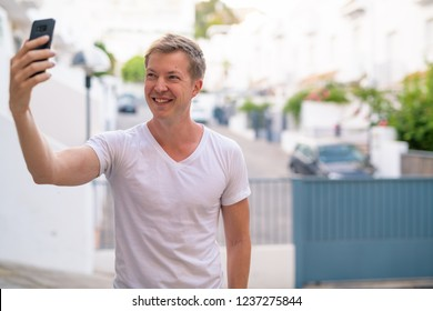 Young Handsome Man Smiling While Taking Selfie Outdoors