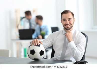 Young handsome man with soccer ball in office