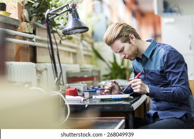 Young handsome man soldering a circuit board and working on fixing hardware