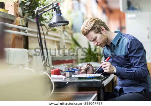 Junge, gut aussehende Person, die eine Leiterplatte löst und an der Reparatur von Hardware arbeitet