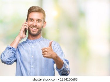 Young handsome man speaking on the phone over isolated background happy with big smile doing ok sign, thumb up with fingers, excellent sign