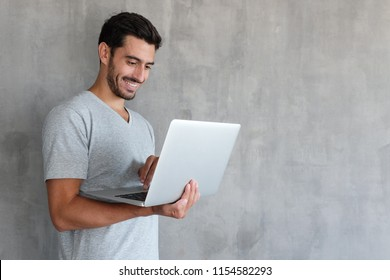 Young handsome man standing against textured gray wall with copy space for ads, holding laptop and watching media with happy smile, sharing web content