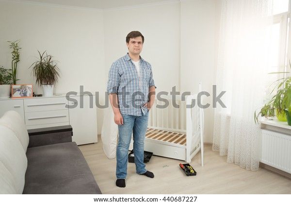 Young handsome man standing at disassembled baby crib at bedroom
