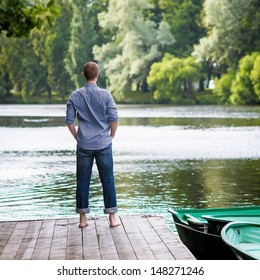 Young handsome man standing on wooden pier, relaxing and meditating in summer morning, back view