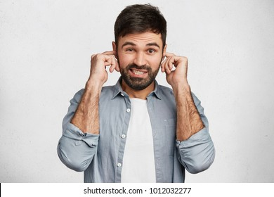 Young handsome man with stubble tries to ignore annoying noise, plugs ears, dressed casually, has displeased expression, isolated over white background. Male refuses to listen something unpleasant