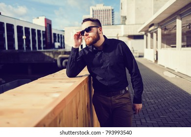 Young handsome man in stylish black clothes and sunglasses.