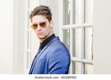 Young handsome man in stylish blue suit looking through sunglasses - Attractive confident male model