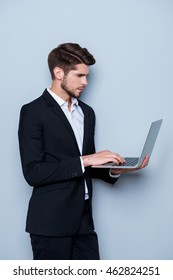 Young handsome man in suit  holding laptop and typing