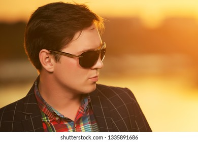 Young handsome man in sunglasses outdoor Stylish trendy male model in black checked blazer
