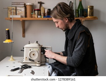 Young handsome man tailor sew fur on furrier machine in workshop