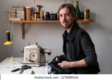 Young handsome man tailor smiling and looking at camera at workplace in sewing workshop