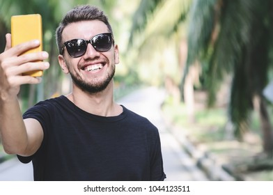 Young handsome man taking selfie on tropical palm road, Koh Phangan, Thailand