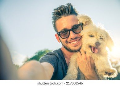 Young handsome man taking a selfie with his dog