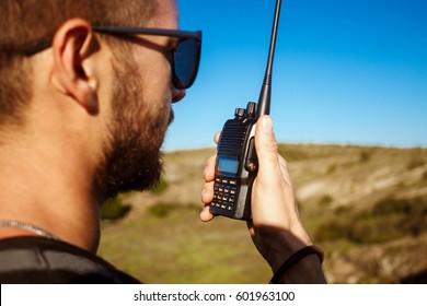 Young handsome man talking on walkie talkie radio, enjoying canyon view.
