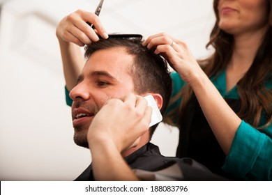 Young handsome man talking over the phone while getting a haircut in a barber shop
