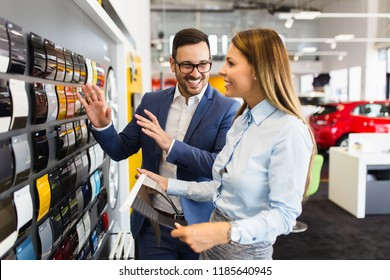 Young handsome man talking with saleswoman and choosing a color for his new car at car showroom.