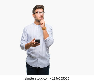 Young handsome man texting using smartphone over isolated background serious face thinking about question, very confused idea