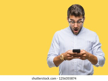 Young handsome man texting using smartphone over isolated background scared in shock with a surprise face, afraid and excited with fear expression