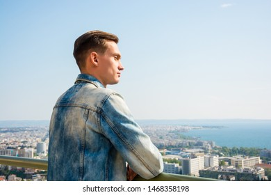 Young handsome man, tourist, near the Upper Town Fortress in the Ano Poli, Thessaloniki, Greece. View of the sea in the Ano Poli