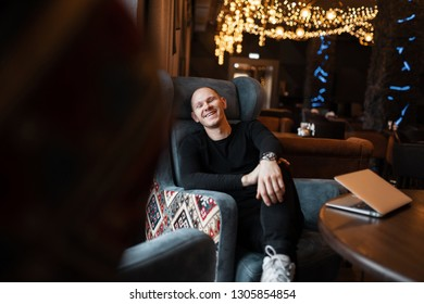 Young handsome man in trendy black clothes sits and laughs at a table on a soft vintage chair in a beautiful expensive restaurant. Funny happy guy resting at lunch time from work.