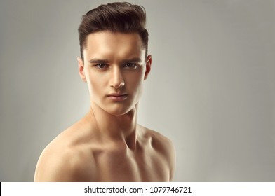 Young handsome man with trendy hairstyle and bare torso.