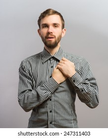 Young handsome man upset keeps his heart, hands on heart. Gesture. On a gray background