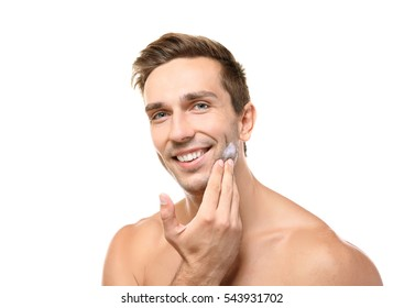 Young handsome man using cream isolated on white