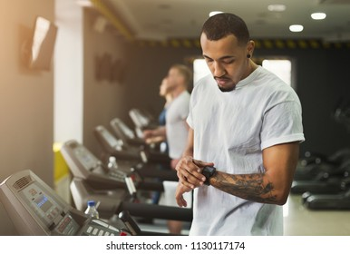 Young handsome man using fitness tracker in sport club. Cardio workout, running on treadmill. Healthy lifestyle, guy training in gym, copy space