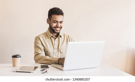 Young handsome man using laptop in office. Businessman or student working on computer online. Freelance, online marketing, education and technology concept