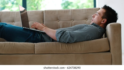Young, handsome man using laptop sitting on sofa