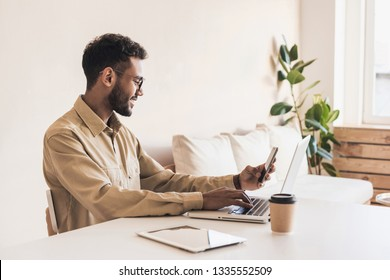 Young handsome man using smart phone and laptop at home. Businessman or student working on computer and texting smartphone. Freelance, education and technology concept