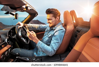 Young handsome man using a smartphone in a convertible car