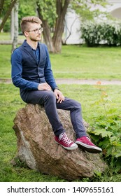 Young, handsome man is waiting to meet sitting on a big stone