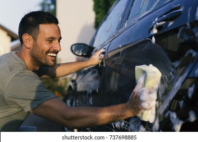 Young handsome man washing car with a sponge and foam