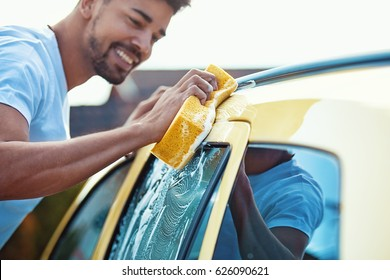 Young handsome man is washing his car.