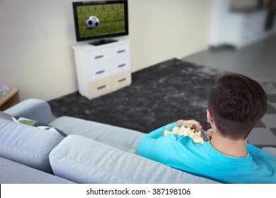 Young handsome man watching TV on a sofa at home