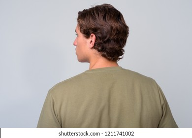 Young handsome man with wavy hair against white background