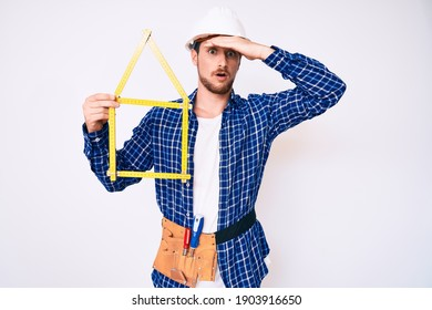 Young handsome man wearing architect hardhat holding build project stressed and frustrated with hand on head, surprised and angry face