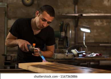 Young handsome man, wearing in black shirt, burning wooden board for displaying textures with petrol blowtorch ignition at factory. Male employee looking at board carefully for producing best pattern.