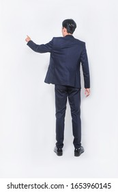 Young handsome man wearing black suit standing shirt over isolated white background Posing backwards pointing ahead with finger hand