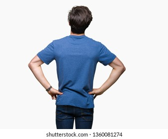 Young handsome man wearing blue t-shirt over isolated background standing backwards looking away with arms on body