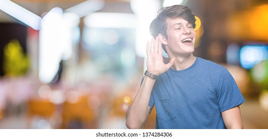 Young handsome man wearing blue t-shirt over isolated background smiling with hand over ear listening an hearing to rumor or gossip. Deafness concept.