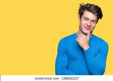 Young handsome man wearing blue sweater over isolated background with hand on chin thinking about question, pensive expression. Smiling with thoughtful face. Doubt concept.