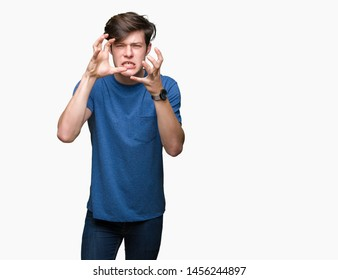 Young handsome man wearing blue t-shirt over isolated background Shouting frustrated with rage, hands trying to strangle, yelling mad