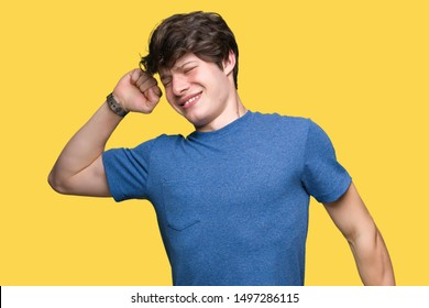 Young handsome man wearing blue t-shirt over isolated background stretching back, tired and relaxed, sleepy and yawning for early morning